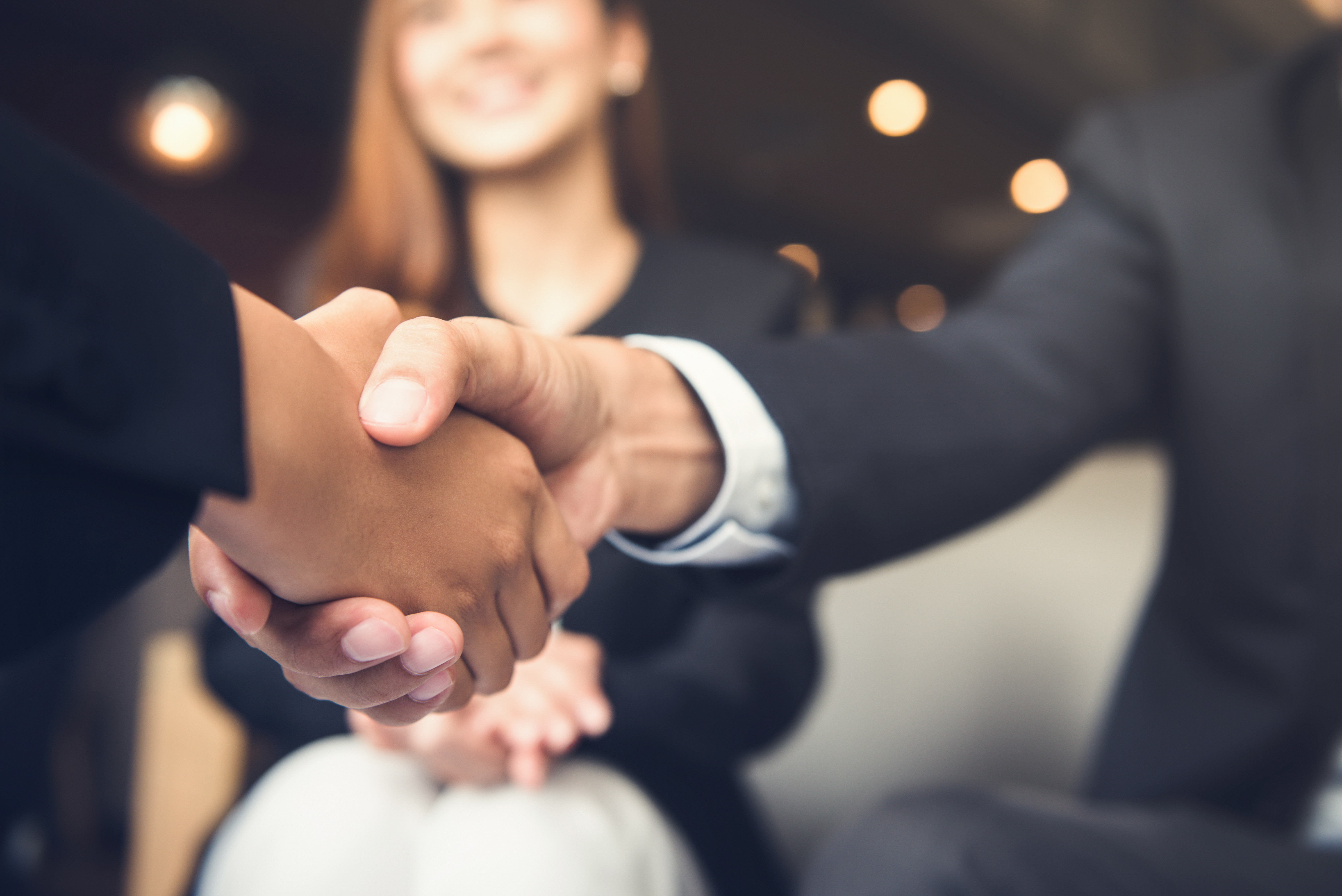 Two people shaking hands in trust